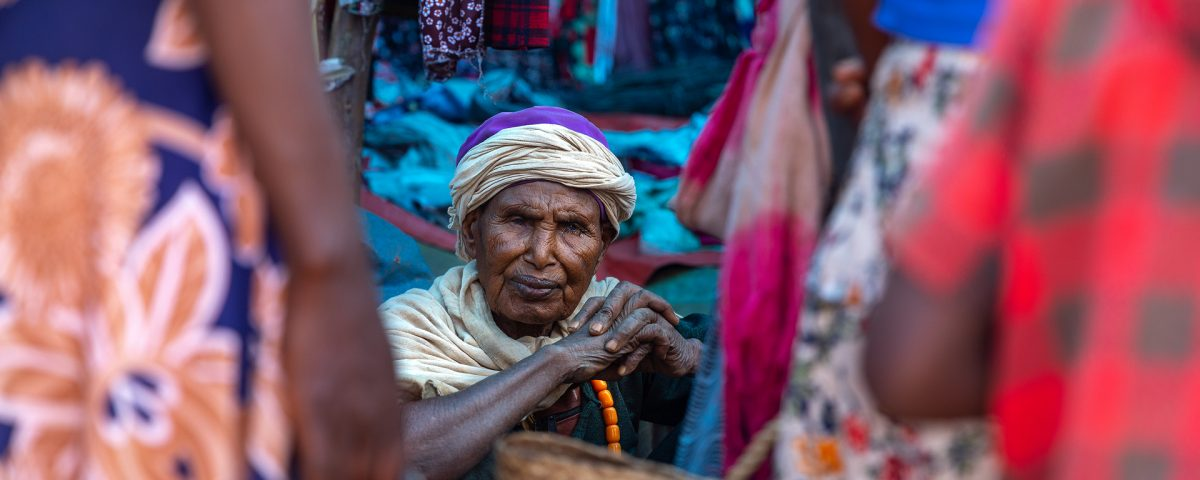 An old woman in a colourful market