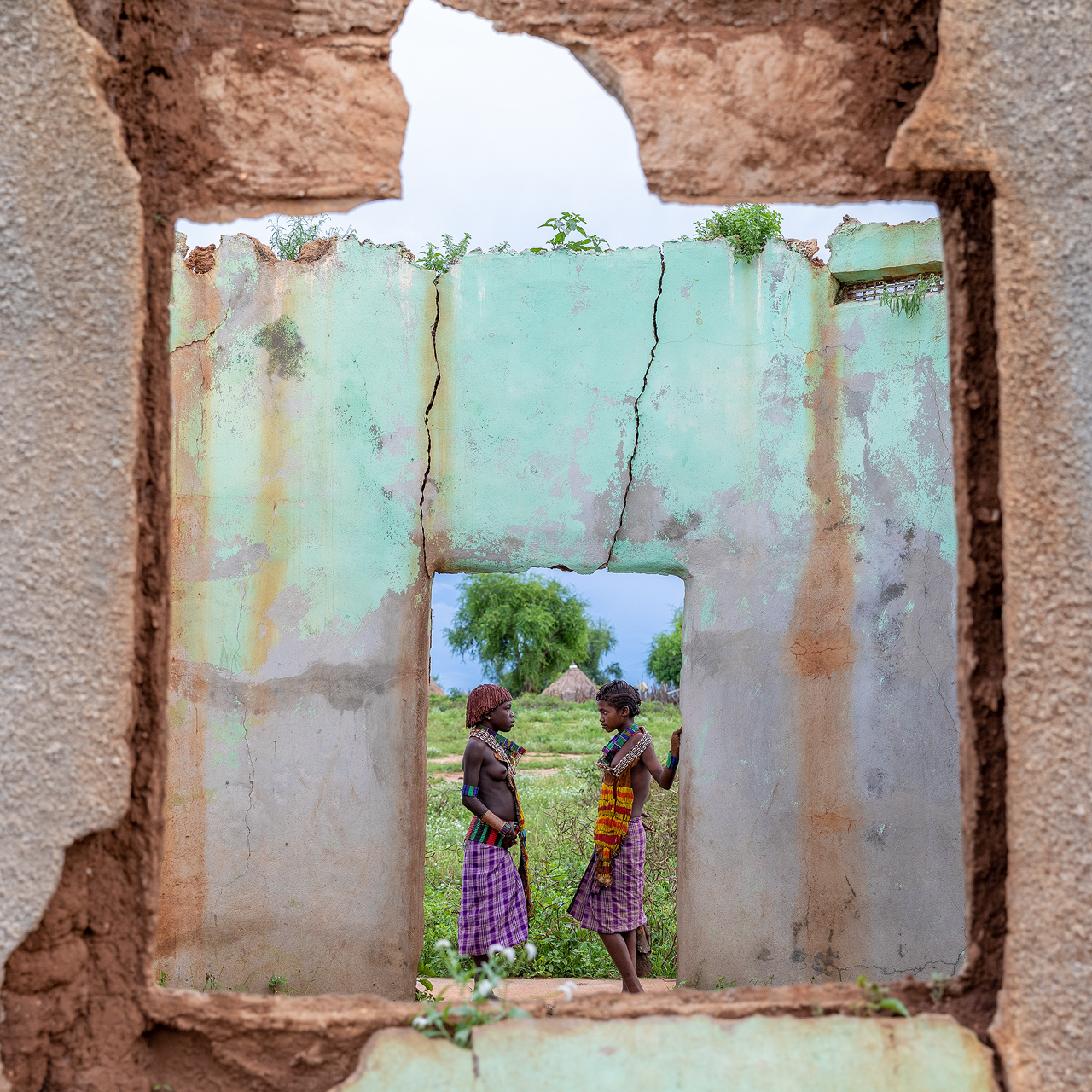 Two African girls talking in a ruined building