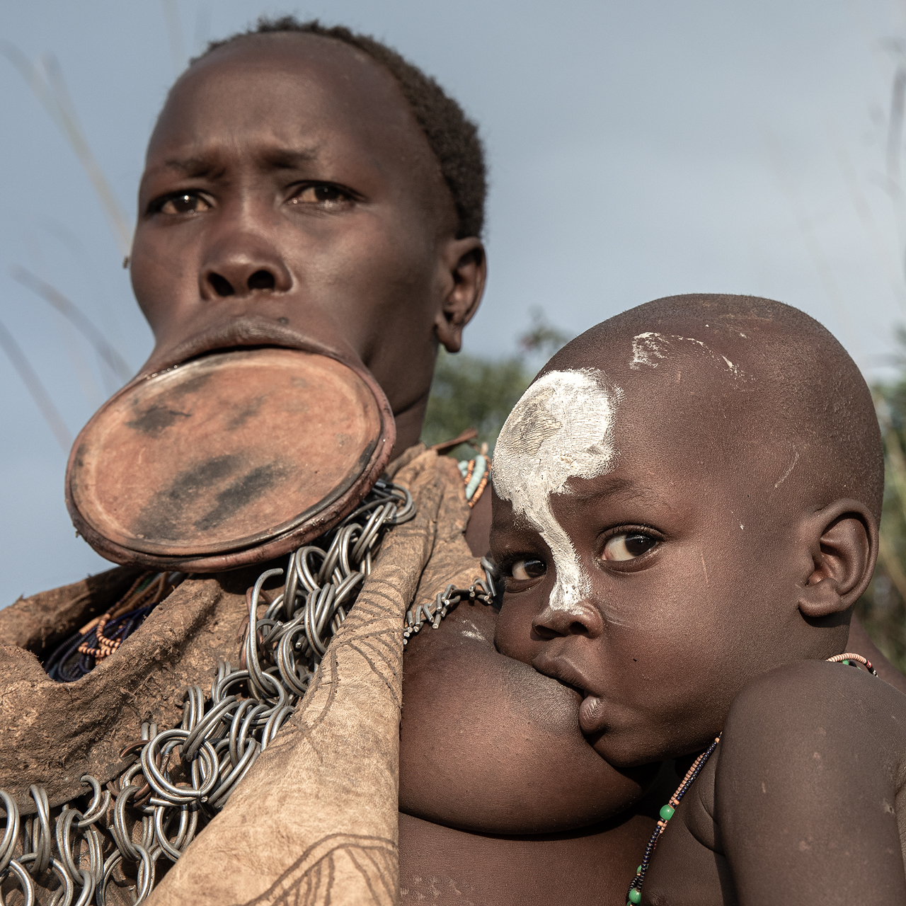 A Suri woman breast feeding infant