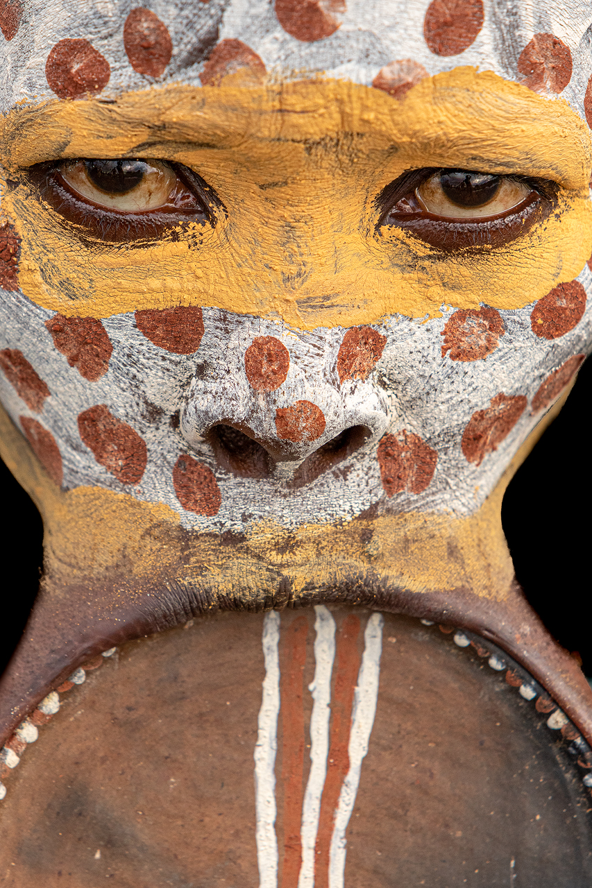 A woman with face paint and lip plate