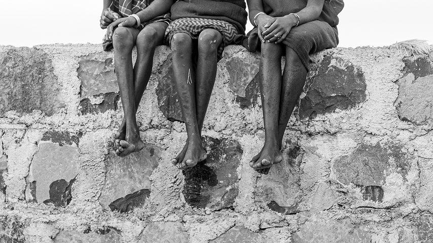 Suri girls sitting on a wall