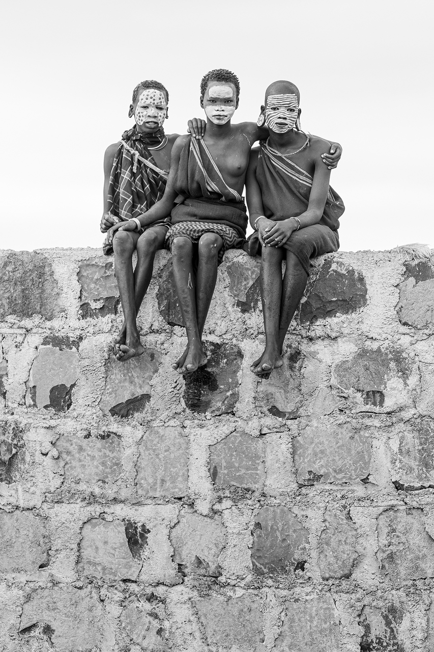 Suri girls sitting on a wall