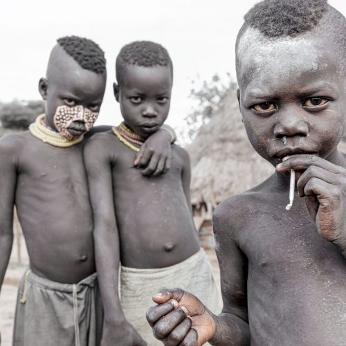 Three young African boys, one smoking a cigarette