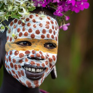 Suri Girl with flowers and face paint laughing and smiling