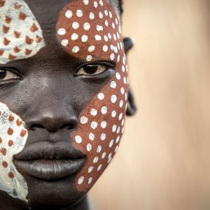 A Suri girl with face paint staring at the camera